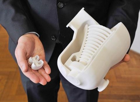 Das Foto zeigt die Nahaufnahme von zwei männlichen Händen. In der einen Hand hält er eine sehr kleine 3D-gedruckte Turbine. In der anderen Hand hält er eine etwa zehnmal größere 3D-gedruckte Turbine.