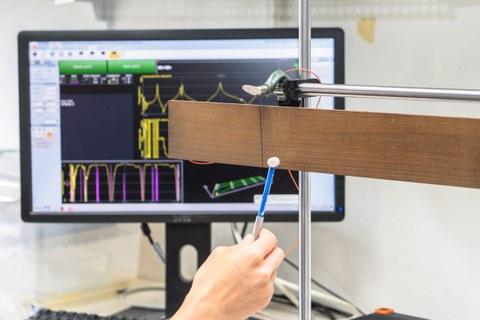 Ein Brett ist horizontal in eine Halterung eingespannt. Man sieht eine Hand, die einen kleinen Hammer hält, der gerade auf das Holz klopft. Im Hintergrund steht ein Monitor, der verschiedene mehrfarbige Kurven zeigt. Damit testen die Wissenschaftler die Schwingungseigenschaften von thermisch behandeltem Ahorn. Diese sind entscheidend für die Klangqualität.