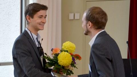 Das Foto zeigt, wie ein junger Mann im Anzug gerade einen Blumenstrauß an Mauritz Mälzer übergibt. Er trägt ebenfalls einen dunklen Anzug und freut sich sichtlich über den Preis.