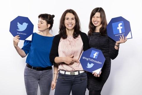 """Drei junge Frauen stehen nebeneinander vor einem weißen Hintergrund. Alle drei halten ein achteckiges Schild in der Hand. Auf den Schildern steht die Webadresse der Social-Media-Kanäle """"@ingTUDresden""""."""