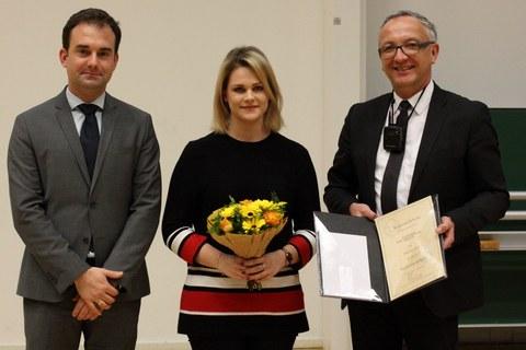 Drei Personen stehen nebeneinander, in der Mitte eine junge Frau. Sie hält Blumen in der Hand. Der Mann rechts neben ihr hält eine aufgeklappte Urkunde in der Hand.