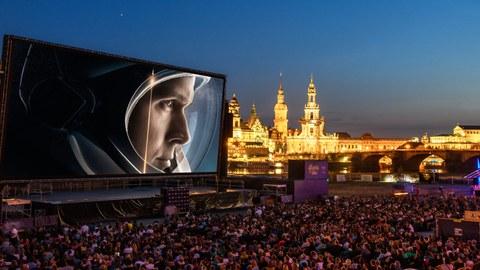 """Das Foto zeigt die Kulisse der Filmnächte am Elbufer in Dresden. Auf der großen Leinwand sieht man einen Ausschnitt des Filmes """"Aufbruch zum Mond""""."""