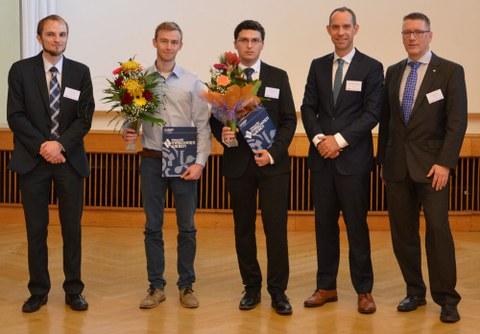 Das Foto der feierlichen Preisverleihung zeigt fünf Personen nebeneinander. Der zweite und dritte Mann von links halten Blumen und Urkunden in der Hand.