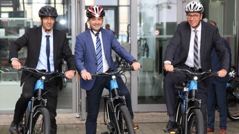 Das Foto zeigt drei Professoren, die gerade mit einem Elektrofahrrad losfahren wollen. Jeder trägt einen Fahrradhelm.