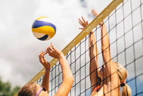 Zwei Frauen spielen Volleyball. Beide haben ihre Arme weit oben bzw. über dem Netz. Der Ball befindet sich in der Luft. Das Foto ist eine Nahaufnahme. Das Volleyballnetz geht vom linken unteren Bildrand bis zum rechten oberen Rand.