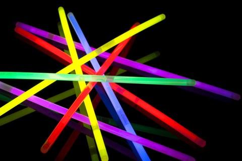 Das Foto zeigt bunte Leuchtstäbe vor schwarzem Hintergrund.