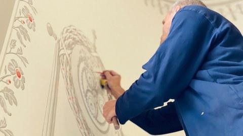 Das Farbfoto zeigt einen Restaurator im blauen Kittel, der gerade ein Motiv auf eine Wand malt.