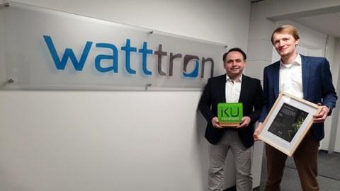 """Das Foto zeigt zwei junge Männer in Jackets, die rechts neben einem Schild stehen. Auf dem Schild steht """"watttron"""". Es ist an einer Flurwand angebracht. Der linke Mann hält eine Preisskulptur in den Händen, der größere MAnn rechts neben ihm eine Urkunde."""
