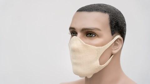 Das Foto zeigt einen männlichen Modellkopf, der eine gestrickte Mund-Nasen-Maske trägt.