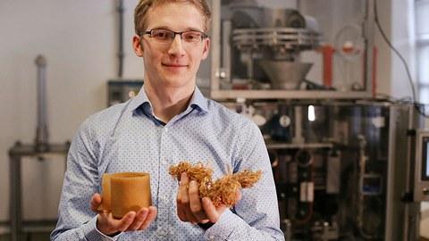 Das Foto zeigt den Nachwuchswissenschaftler Ludwig Schmidtchen, der in seinen Händen hellbraune, getrocknete Algen hält. Im Hintergrund ist eine Laborapparatur zu sehen.