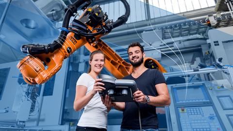 Auf dem Bild sind zwei Studierende an einem Roboter-Greifarm zu sehen