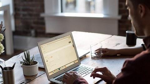 Auf dem Bild ist ein junger Mann am Laptop zu sehen