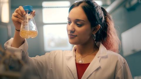 Auf dem Bild ist einer Studierende zu sehen, die sich ein Reagenzglas anschaut