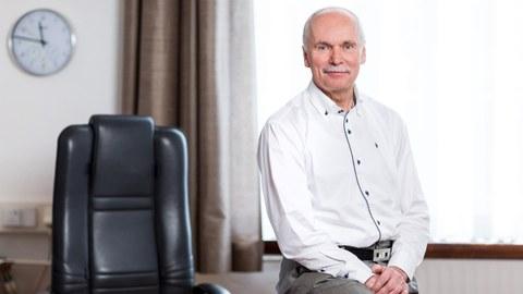 Das Foto zeigt Prof. Ralph Stelzer, der seitlich auf seinem Dekane-Schreibtisch sitzt. Er trägt ein weißes Hemd und eine graue Hose.
