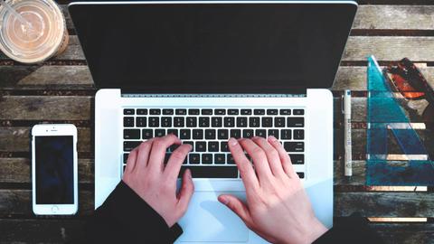 Auf dem Bild sind die Hänge eines Mannes an einem Laptop, ein Smartphone, ein Lineal, eine Sonnenbrille und ein Milchshake zu sehen