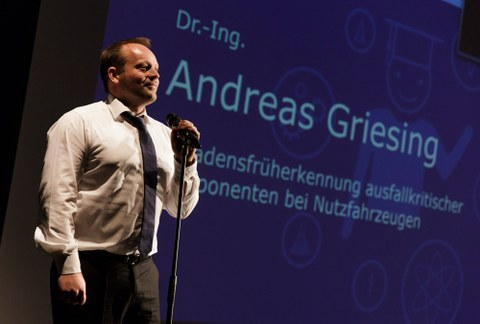 Der Gewinner des ersten Science-Slams der Fakultät Maschinenwesen, Dr. Andreas Griesing, auf der dunkelblauen Bühne des Boulevardtheater Dresden. Gleich spricht er in das Mikrophon, das vor ihm steht und beginnt seinen dreiminütigen Auftritt.