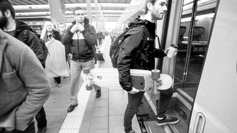 Ein junger Mann steigt in die U-Bahn ein und hält ein Skateboard unterm Arm.