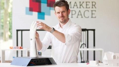 Juniorprofessor Jens Krzywinski steht an einer Handplastik im Makerspace der Sächsischen Landesbibliothek – Staats- und Universitätsbibliothek Dresden..