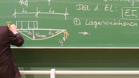 Foto: eine Tafel in einem Lehrraum an der ein Mann etwas anschreibt. Dieser steht ganz links, ist nur von hinten und nicht vollständig zu sehen.