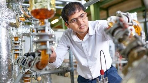 Foto mit einem Ausschnitt einer Absorbtionsanlage, einer Versuchsanlage im Technikmaßstab. Ein Mitarbeiter ist zu sehen, der an dieser Anlage etwas einstellt oder zu kontrolliert.