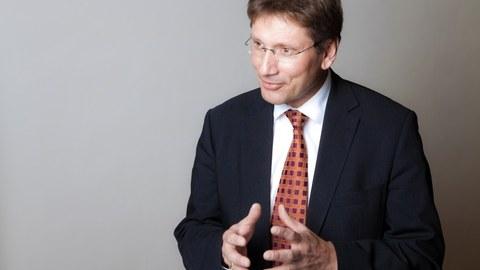 lebhaftes Foto von Professor Michael Beckmann wie er etwas erklärt und seine Hände bewegt