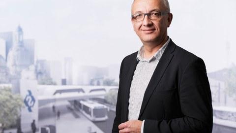 Foto von Professor Jens-Peter Majschak vor dem Hintergrund einer virtuellen Stadtlandschaft