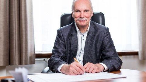 Foto von Professor Ralph Stelzer, er sitzt an einem Schreibtisch und blickt neugierig in Richtung des Betrachters