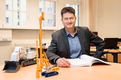 Foto von Professor Frank Will an einem Tisch auf dem 2 Modelle von Baumaschinen stehen