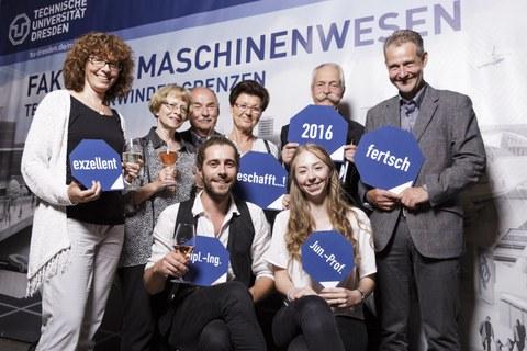 Foto: 8 Personen stehen vor einem Plakat der Fakultät Maschinenwesen, freuen sich und halten 6 blaue Schilder in den Händen auf denen steht: exzellent; geschafft; 2016; fertsch; Dipl.-Ing und Jun.-Prof.