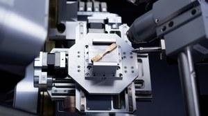 Foto. Ein Prüfgegenstand aus Metall ist in eine Vorrichtung eingespannt und wird zur Werkstoffprüfung geröntgt