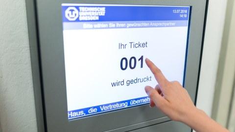 Foto: des Ticketsystems für das Prüfungsamt, auf dem Bildschirm ist zu sehen: ihr Ticket 001 wird gedruckt