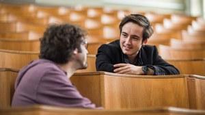 Foto: Blick in einen Hörsaal, im Vordergrund sind 2 männliche Personen zu sehen, die sich angeregt unterhalten
