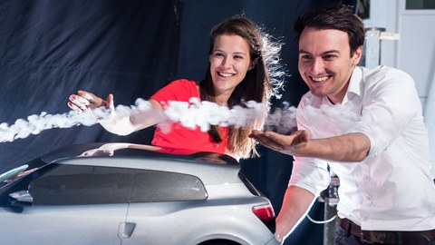 Foto: 2 Studierende blicken begeistert auf ein Modellauto, das von einer sichtbaren Luftströmung umflossen wird