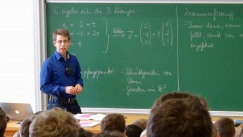 Dieses Bild zeigt den Mathematikdozenten Christoph Laabs während einer Vorlesung im Hörsaal vor der Tafel.