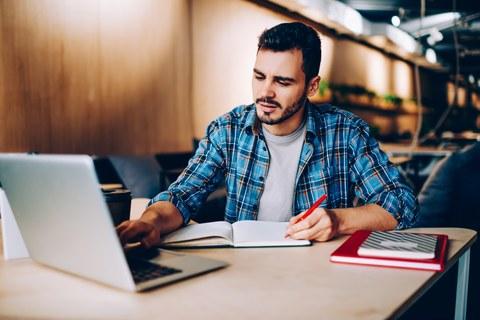 Das Foto zeigt einen jungen Mann, der an einem Tisch sitzt. Während er mit einer Hand auf seinem Laptop tippt, schreibt er mit der anderen etwas in ein Notizbuch.
