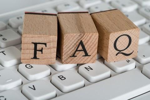 Auf dem Bild sind drei auf einer Tastatur liegende Buchstabenstempel mit den Buchstaben F A Q zu sehen.