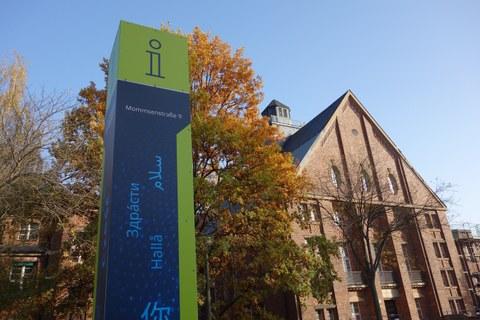 """Das Foto zeigt eine Gebäude und eine Informationssäule an der Mommsenstraße 9. Auf der Informationstafel ist das Wort """"Hallo"""" in verschiedenen Sprachen geschrieben. Die Blätter des Baumes im Hintergrund sind bunt gefärbt."""