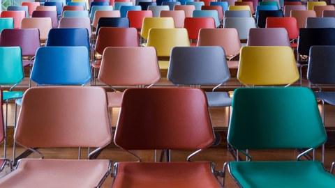 Auf dem Bild sind Stuhlreihen mit leeren Stühlen zu sehen.
