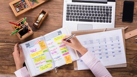 Das Bild zeigt die Draufsicht eines Schreibtisches, an dem jemand arbeitet. Auf dem Schreibtisch liegen neben verschiedenen Büroutensilien ein Notebook und ein Kalender, in den die Person etwas einträgt.