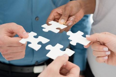 Zu sehen sind die Ausschnitte mehrerer Personen, die je ein Puzzelteil in der Hand halten. Sie versuchen gemeinsam, das Puzzle zusammen zu setzen.