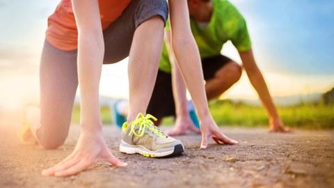 Das Bild zeigt zwei Läufer in Startposition aus der Froschperspektive.