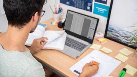 Das Foto zeigt einen Studenten an seinem Schreibtisch. Vor ihm steht sein Laptop und viele weitere Büromaterialien. Mit einem Stift notiert er gerade etwas auf einem Block.