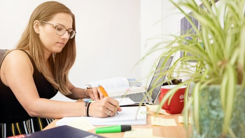 Das Foto zeigt eine Studentin an ihrem Schreibtisch. Vor ihr steht ihr Laptop und viele weitere Büromaterialien. Mit einem Stift notiert sie gerade etwas auf einem Block.