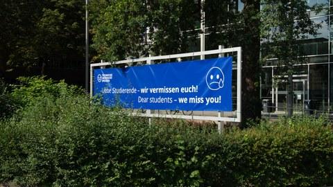 """Auf dem Bild ist ein Banner mit der Aufschrift """"Wir vermissen euch"""" zu sehen, welches vor dem Hörsaalzentrum steht."""