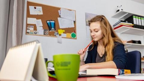 Das Bild zeigt eine Studentin am Schreibtisch. Im Hintergrund ist die Einrichtung zu sehen, die in Wohnheimen anzutreffen ist.