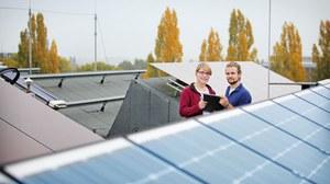Foto der Photovoltaikanlage auf dem Dach des Zentrums für Energietechnik. Im Vordergrund sieht man Solarpanele, im Hintergrund zwei Personen.