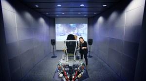 Das Foto zeigt den Blick in das Multimodale Messlabor der Fakultät Elektrotechnik und Informationstechnik. Im Zentrum des Bildes sieht man zwei Personen. Eine Person sitzt aufdem Versuchsaufbau, die zwei unterstützt und erklärt die Handhabung.