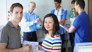 Auf dem Foto sieht man eine Gruppe von Studierenden, die sich mit einem Lehrenden austauschen.