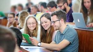 Das Foto zeigt Studierende im Hörsaal. Im MIttelpunkt des Betrachters stehen drei Studierende, die gemeinsam auf ein Tablett schauen.