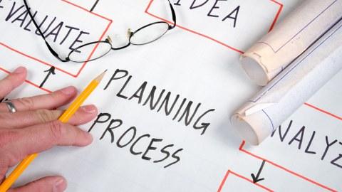 Das Foto zeigt ein Blatt mit einem Ablaufdiagramm zum Thema Planungsprozess. In der unteren linken Ecke ist eine Hand zu sehen, die einen Bleistift hält, darüber liegt eine Brille.